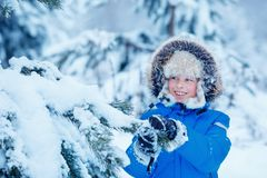 Cute little boy wearing warm clothes playing on winter forest Royalty Free Stock Image