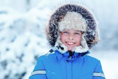 Cute little boy wearing warm clothes playing on winter forest Stock Photos