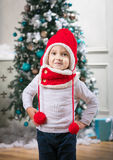 Cute little boy wearing winter hat and scarf while standing against Christmas tree Stock Images