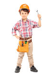Cute little boy wearing working clothes and holding a wrench Stock Images
