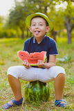 Cute little boy width watermelon sitting on grass outdoor Royalty Free Stock Photography