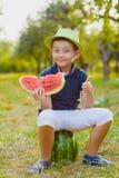 Cute little boy width watermelon sitting on grass outdoor Stock Images