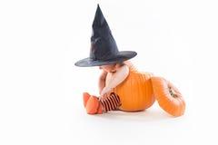 Cute little boy in witch hat sitting inside big pumpkin Royalty Free Stock Photos