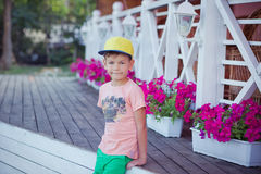 Cute little boy on wood close to purple flowers on beautiful summer day stylish dressed. stock photos