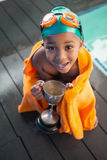 Cute little boy wrapped in towel with trophy poolside Royalty Free Stock Photos