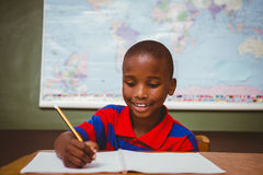 Cute little boy writing book in classroom. Portrait of cute little boy writing book in classroom Stock Photos