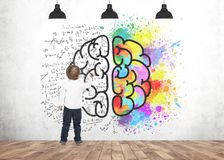 Cute little boy writing drawing marker brain. Rear view of a cute little boy wearing a white shirt and dark blue jeans writing or drawing with a marker. A Stock Image