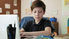 Cute little boy writing essay for school in his room doing homework stock video footage