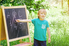 Cute little boy writing letters and numbers at blackboard in the garden. Royalty Free Stock Photos