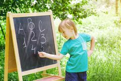 Cute little boy writing letters and numbers at blackboard in the garden. Back to school concept Stock Photos