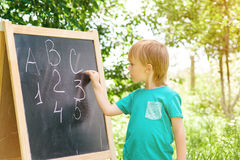 Cute little boy writing letters and numbers at blackboard in the garden. Stock Photos