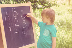 Cute little boy writing letters and numbers at blackboard in the garden. Toned. Royalty Free Stock Images