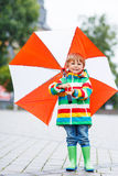 Cute little boy with yellow umbrella and colorful jacket outdoor Stock Image