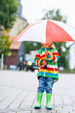 Cute little boy with yellow umbrella and colorful jacket outdoor Royalty Free Stock Photo
