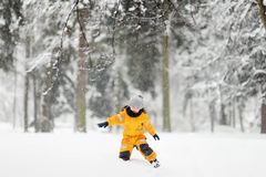 Cute little boy in yellow winter clothes walks during a snowfall stock image