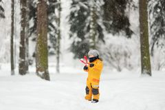 Cute little boy in yellow winter clothes walks in during a snowfall and using a plastic toy makes snowballs stock image