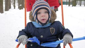 Cute little boy and young mother play in the winter with snow in the park. Blue kid`s jacket and red at mom. stock video footage
