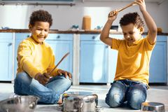 Cute little boys creating noise by drumming on saucepans. Friendship goals. Joyful little boys sitting cross-legged on the kitchen floor and creating noises by Royalty Free Stock Photos