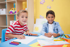 Cute little boys drawing at desk Royalty Free Stock Images