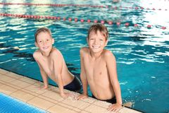 Cute little boys in indoor pool. Cute little boys in indoor swimming pool royalty free stock photos