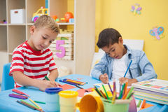 Cute little boys making art together in classroom. At the nursery school royalty free stock photo