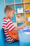 Cute little boys painting at table in classroom Stock Photo