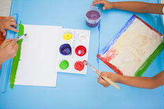 Cute little boys painting at table in classroom Royalty Free Stock Image