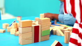 Cute little boys playing with building blocks at table stock footage