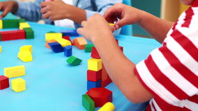 Cute little boys playing with building blocks at table stock video footage