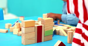 Cute little boys playing with building blocks at table stock video