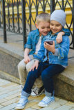 Cute Little Boys playing with cell phone in city. Cute Little Boys playing with cell phone outdoors in city on beautiful spring day royalty free stock image