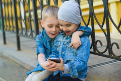 Cute Little Boys playing with cell phone in city. Cute Little Boys playing with cell phone outdoors in city on beautiful spring day stock image