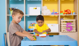 Cute little boys playing with modelling clay in classroom Stock Image