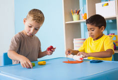 Cute little boys playing with modelling clay in classroom Royalty Free Stock Photography