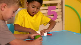 Cute little boys playing with modelling clay in classroom stock footage