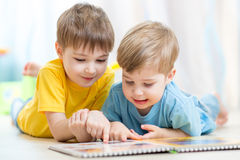 Cute little boys read book together stock image