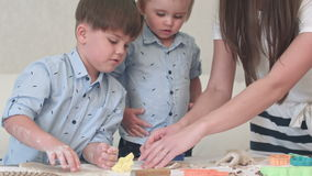 Cute little boys rolling dough for the cookies together with mom stock video footage
