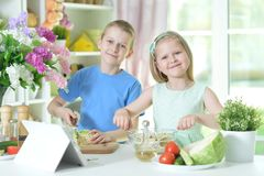 Cute little brother and sister cooking. Together at kitchen Royalty Free Stock Photo