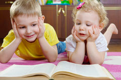 Cute little brother and sister reading book on floor Royalty Free Stock Photography