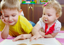Cute little brother and sister reading book on floor Royalty Free Stock Images