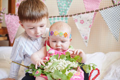 Cute little brother and sister sitting on the bed in their room Royalty Free Stock Photos