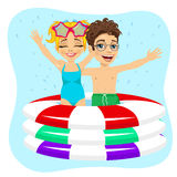 Cute little brother and sister swimming in inflatable pool. On blue background Royalty Free Stock Photo