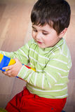 Cute little brunette child is playing with toys Stock Photography