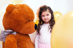 Cute little brunette posing with big teddy bear Royalty Free Stock Photos