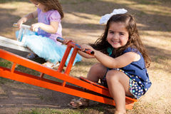 Cute little brunette in a seesaw Stock Photography
