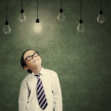 Cute little businessman looking at lit bulb Stock Images