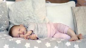Cute little carefree baby sleeping surrounded by soft pillow lying with closed eyes full shot. Relaxing barefoot child enjoying serene dream having good time stock footage