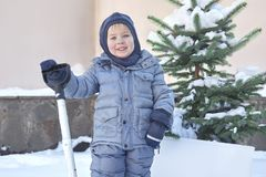 Cute little caucasian baby boy shovels snow in the yard with fir-tree on background. Winter outdoors, smiling, pink cheeks. Childr. En help, family duties, right royalty free stock photos