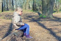Cute little caucasian blond girl sittng on wooden log in forest and looking somewhere. Adorable pensive child dreaming about. Something during walk in park or stock photos
