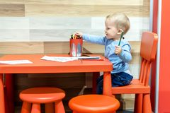 Cute little caucasian blond toddler boy sitting at table and drawing at children area at retail clothes store. Baby spending time royalty free stock photo